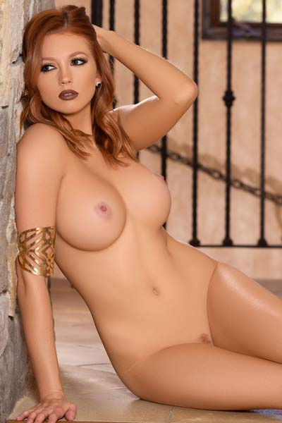 Ravishing redhead Chandler South proudly displays her colossal boobs in sexy high heels