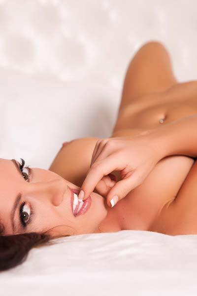 Amazing busty brunette Krystal Lynn undresses slowly in the bedroom