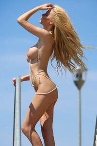 Blonde bombshell displays her sex appealing naked body as she gracefully poses by the sea