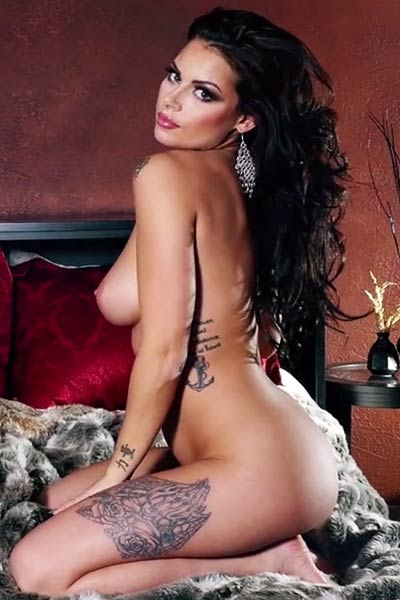 Dark haired Shelly Lee flaunts her large yummy breasts as she poses naked on the bed
