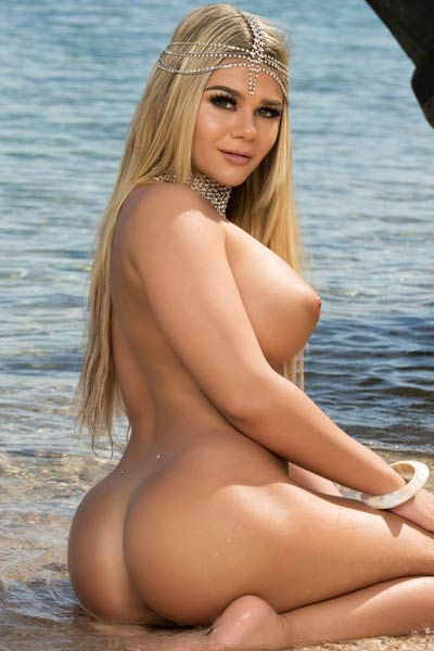 An outdoor photoshoot on the beach with this irresistible blonde with huge seductive boobs