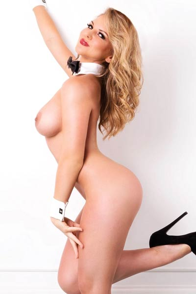This blonde doll bares her large firm tits and sexy long legs for a magazine