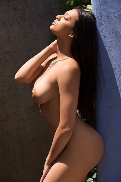 Dark haired seductress bares her large firm tits while posing outdoors