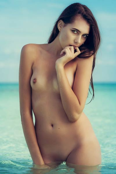 Katrine Pirs take her pink bikini off and poses all naked in shallow water