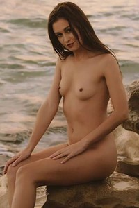 Great young black haired chick Demi Fray seductively poses naked on rock