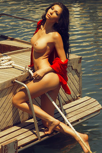 Super sexy brunette is posing naked on the yacht leaving us speechless with big fake boobs