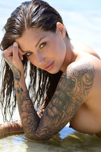 Tattooed babe with nice boobs flashing with her curves on the rocks by the sea