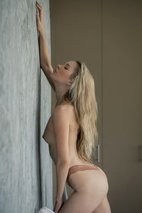 Blonde hottie gives us a nice view on her perky tits and peachy ass while she is posing naked