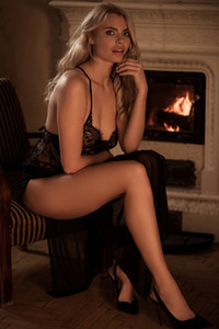 Outstanding blonde sweetie displays her marvelous curves by the fireplace