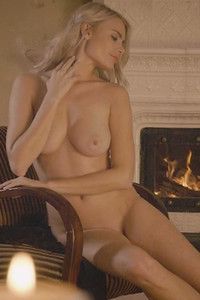 Angelic blonde Miky Muse takes her black bodysuit off and poses naked by the fireplace
