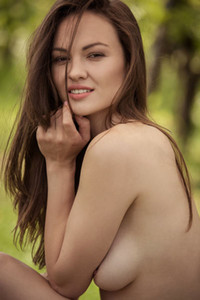 Beautiful Rita Y uninhibitedly poses naked in the garden teasing with her tender smile