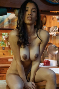 Busty Ebony model presenting her natural assets as she undresses in an indoor photoshoot